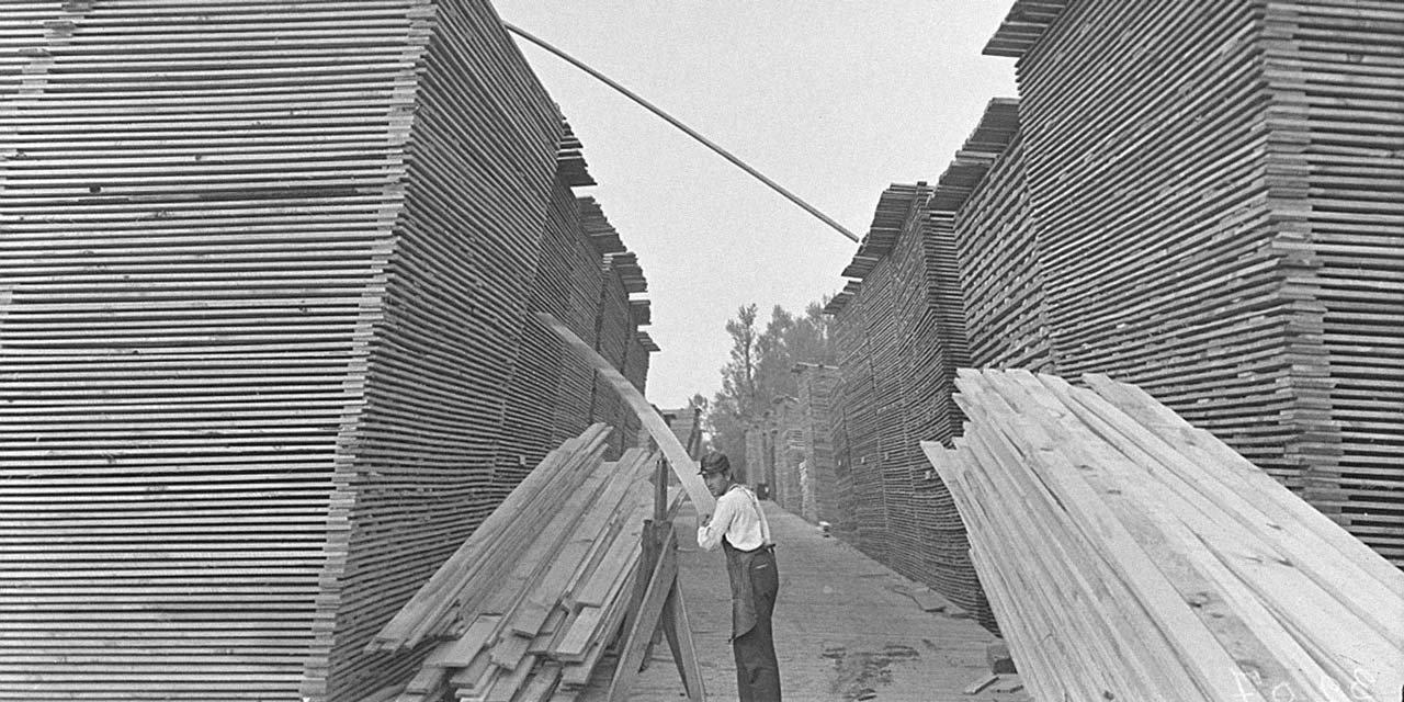 Lumber yard worker sorting through stacks of planks of wood