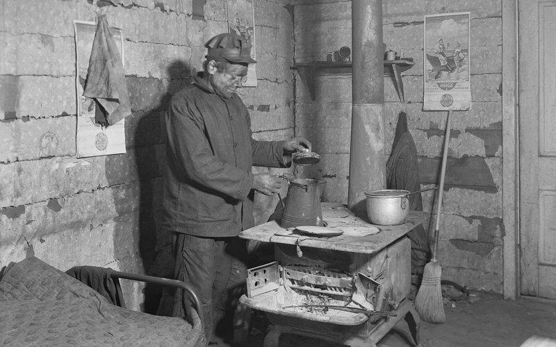 Coal miner preparing a pot of tea inside a workers hut