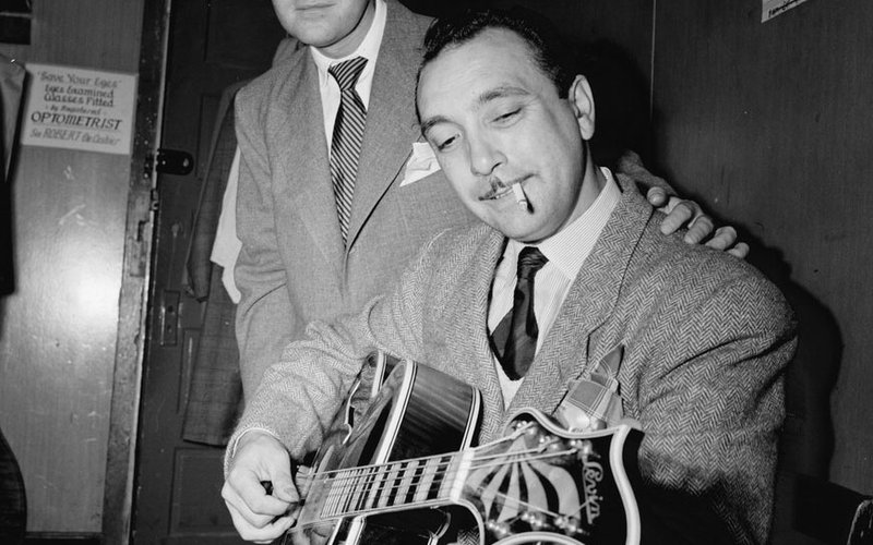 Photo of Django Reinhardt playing a guitar