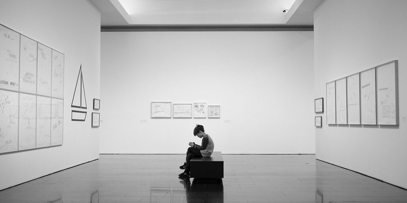 Young boy seated inside an art gallery and using a mobile device