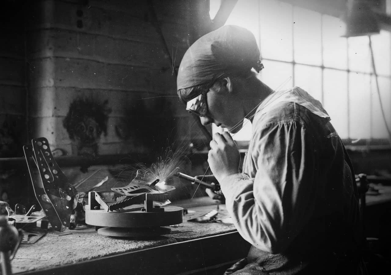 Vintage black and white photo of a woman welding metal components together.