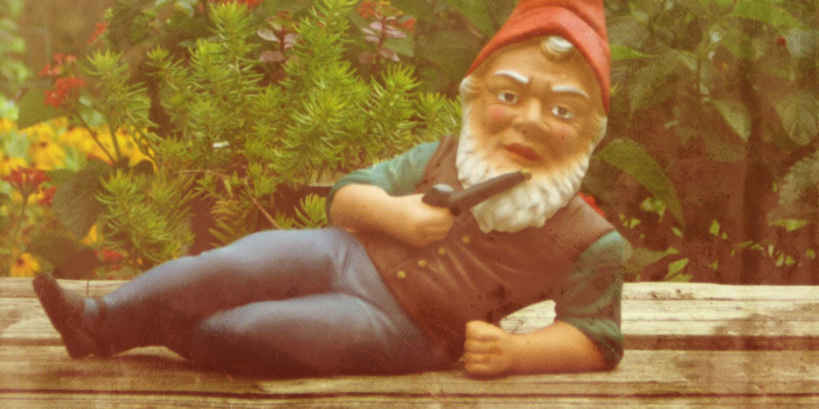Statue of a reclining garden gnome smoking a pipe