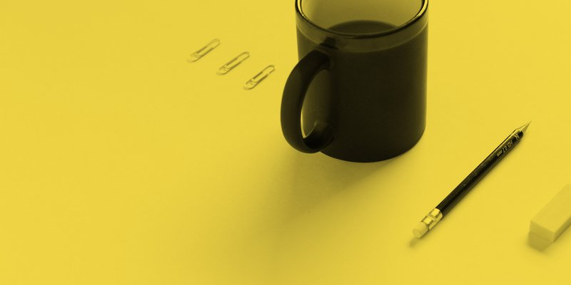 Three paper clips, a pencil, an eraser and a mug of coffee on an office desk