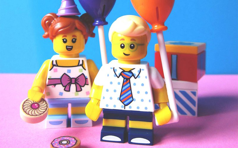 Two Lego mini-figures holding balloons and cake in front of wrapped presents