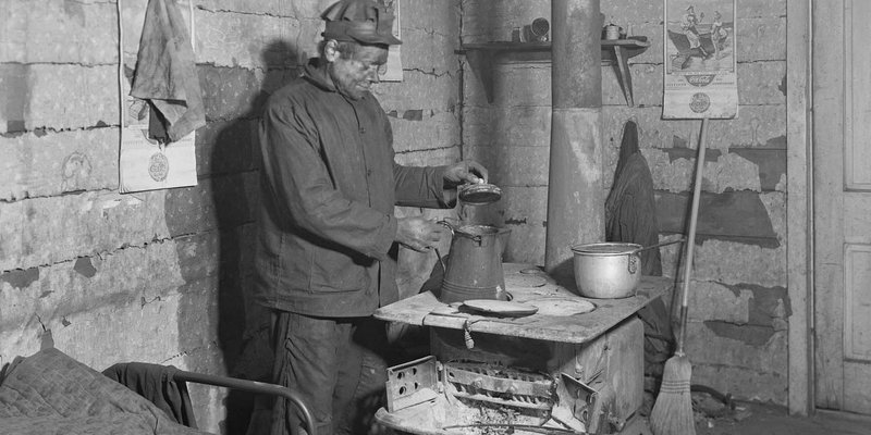Coal miner preparing a pot of tea inside a workers hut