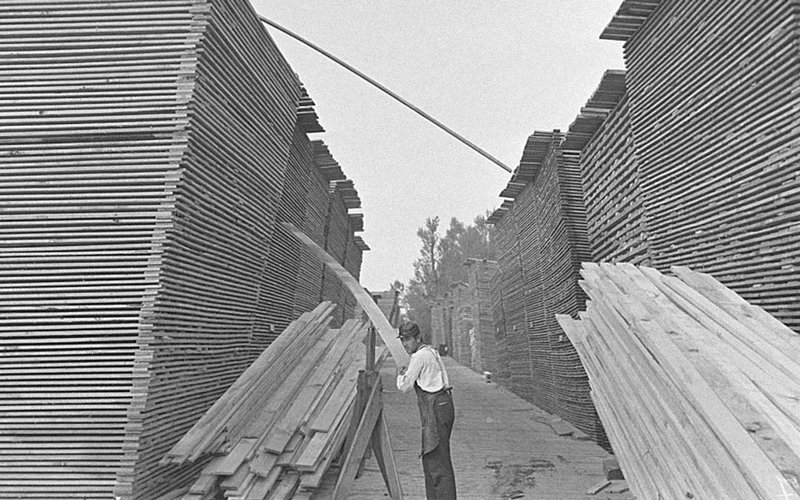 Lumber yard worker sorting through stacks of planks of wood