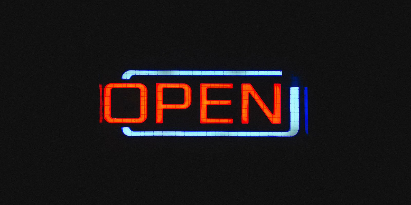Illuminated neon sign of the word 'open' on a dark background