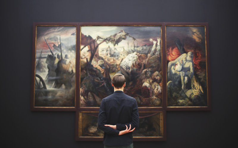 Man looking at an artwork hanging on a gallery wall